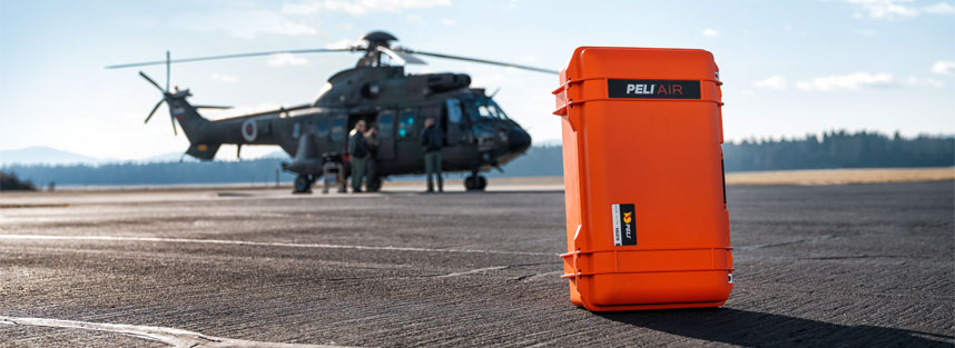 a Peli case with a helicopter in the background