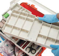 close up of a man in blue medical gloves pulling out the Customisable Pullout Trays on an orange peli air 1465ems case
