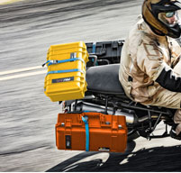 a man riding a motorbike with 3 peli air 1615 strapped to the back to show they are dustproof