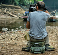 photographer sat on an explorer case near a river taking a picture