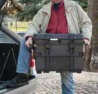 a man lifting two explorer 5140 tool cases into the boot of a car