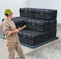 A member of the military checking peli 0550 transport cases on a pallet