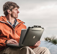 Man in an orange coat outdoors using a Peli 1070cc laptop case