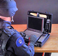 a man in miltary gear using a peli 1470 laptop case which fits laptops up to 13 inches