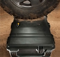 close up of peli 0370 cube case under a wheel of a vehicle