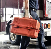 Paramedic carrying an orange Peli 1460ems past an emergecy vehicle