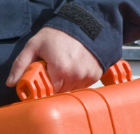 close up of a man holding the rubber over-molded handle of an orange peli 1460em case