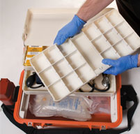 Man with blue medical gloves holding a white tray from a orange peli 1460ems case