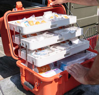 Close up of Orange Peli 1460ems case showing white trays with equipment stored inside
