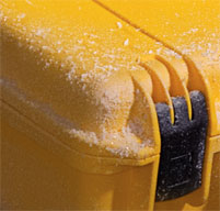 a close up of a peli storm case with snow on the lid to show its dustproof